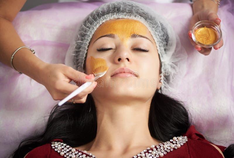 Πορτρέτο του όμορφου κοριτσιού που εφαρμόζει τη χρυσή του προσώπου μάσκα Κινηματογράφηση σε πρώτο πλάνο στοκ εικόνα