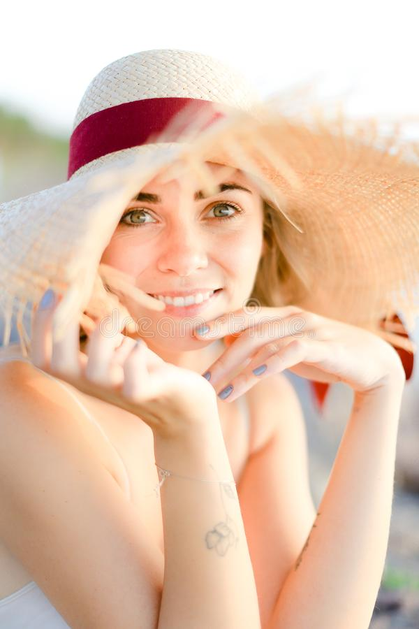 Πορτρέτο του όμορφου κοριτσιού που φορά τη συνεδρίαση καπέλων στην παραλία άμμου στοκ εικόνες με δικαίωμα ελεύθερης χρήσης
