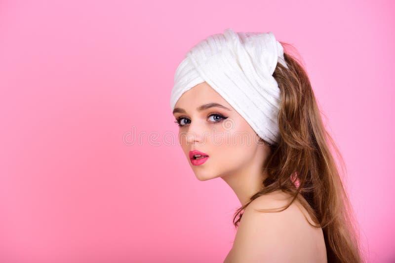 Πορτρέτο του όμορφου κοριτσιού στο μπουρνούζι και με την πετσέτα στο κεφάλι της που καθαρίζει το πρόσωπό της στοκ φωτογραφίες