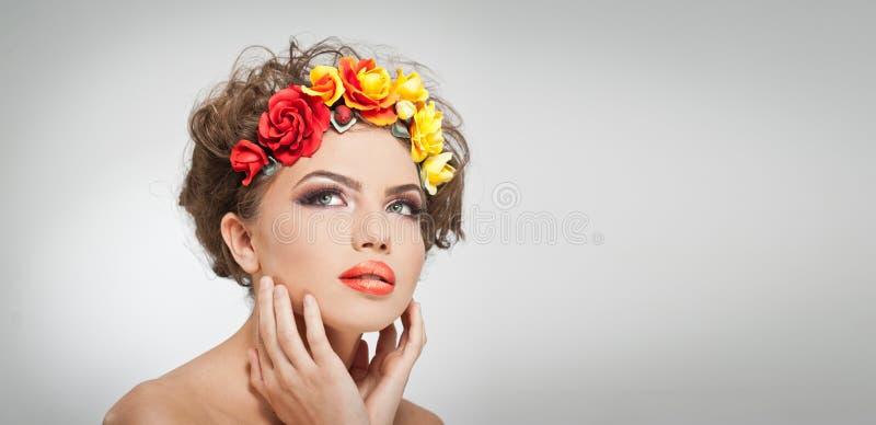 Πορτρέτο του όμορφου κοριτσιού στο στούντιο με τα κίτρινα και κόκκινα τριαντάφυλλα στην τρίχα και τους γυμνούς ώμους της Προκλητι στοκ εικόνα με δικαίωμα ελεύθερης χρήσης