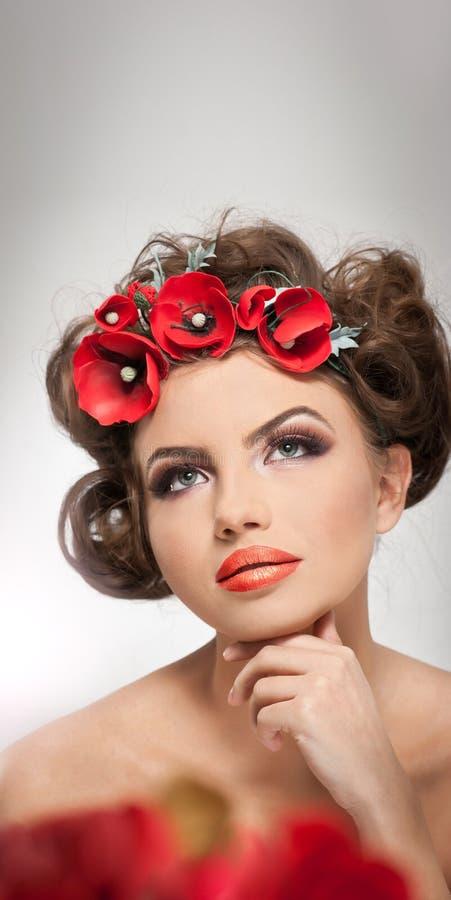 Πορτρέτο του όμορφου κοριτσιού στο στούντιο με τα κόκκινα λουλούδια στην τρίχα της και τους γυμνούς ώμους Προκλητική νέα γυναίκα  στοκ φωτογραφίες με δικαίωμα ελεύθερης χρήσης