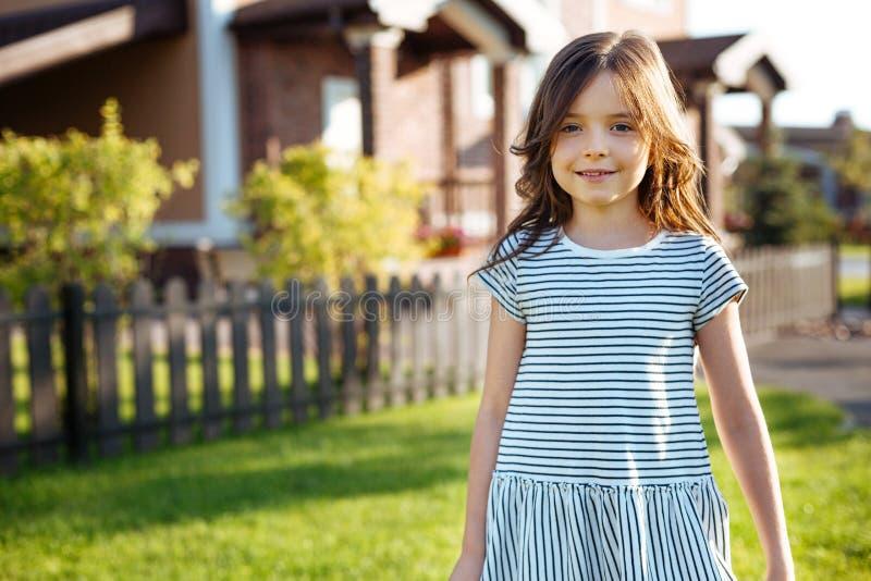 Πορτρέτο του όμορφου μικρού κοριτσιού που στέκεται κοντά στο σπίτι της στοκ φωτογραφίες με δικαίωμα ελεύθερης χρήσης