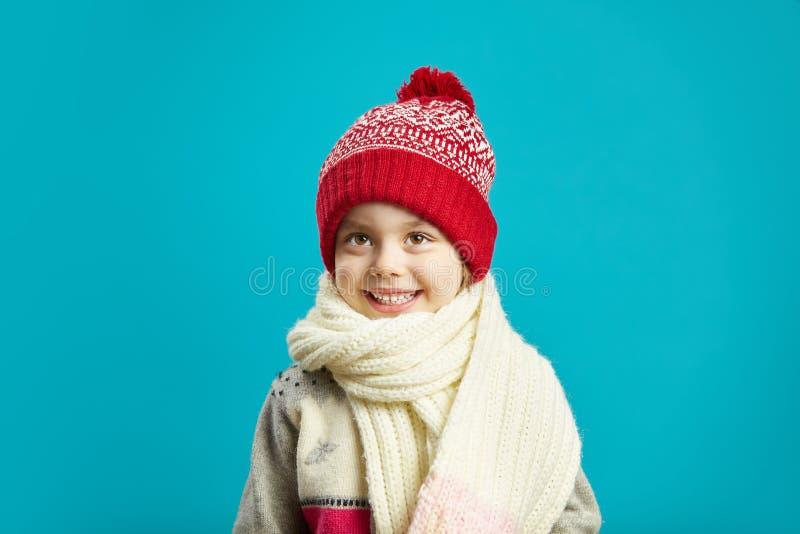 Πορτρέτο του όμορφου μικρού κοριτσιού στο κόκκινο χειμερινό καπέλο στο μπλε υπόβαθρο στοκ εικόνα με δικαίωμα ελεύθερης χρήσης