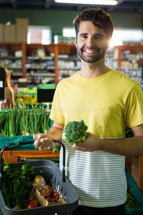 Πορτρέτο του όμορφου μπρόκολου αγοράς ατόμων και των διαφορετικών λαχανικών στο οργανικό τμήμα στοκ εικόνες