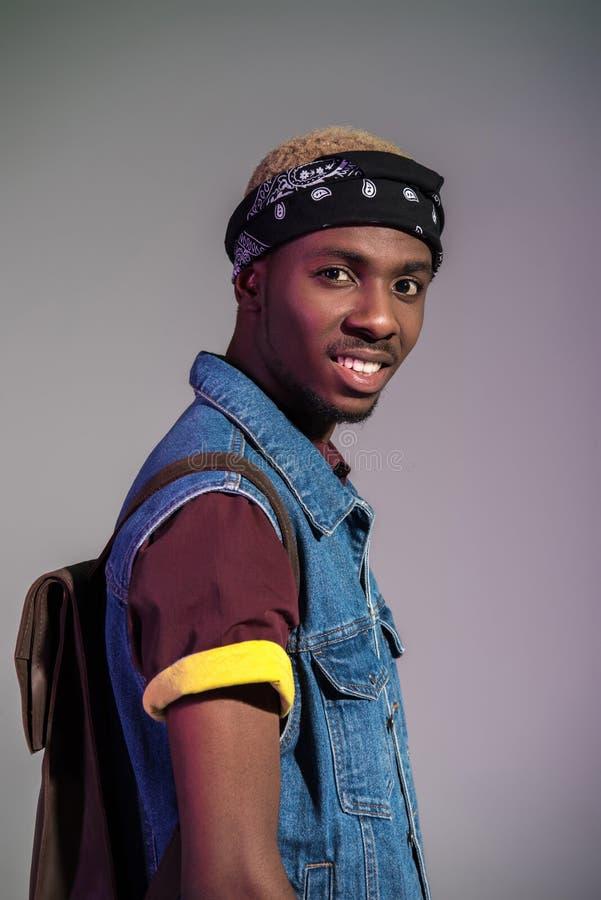 πορτρέτο του όμορφου νέου ατόμου αφροαμερικάνων με το σακίδιο πλάτης δέρματος που χαμογελά στη κάμερα στοκ εικόνα με δικαίωμα ελεύθερης χρήσης