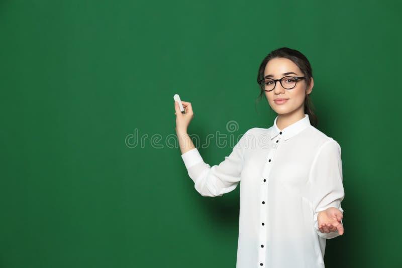 Πορτρέτο του όμορφου νέου δασκάλου κοντά στον πίνακα κιμωλίας στοκ εικόνα