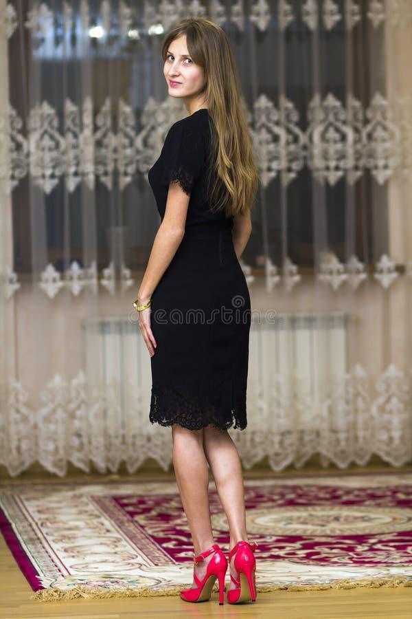 Πορτρέτο του όμορφου νέου κοριτσιού με μακρυμάλλη στο μαύρο φόρεμα α στοκ φωτογραφία με δικαίωμα ελεύθερης χρήσης