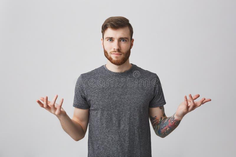 Πορτρέτο του όμορφου νεαρού άνδρα με τη γενειάδα και της δερματοστιξίας στα όπλα διάδοσης βραχιόνων με την ταραγμένη έκφραση, που στοκ εικόνες