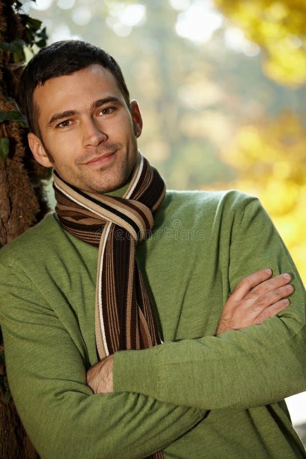 Πορτρέτο του όμορφου νεαρού άνδρα στο πάρκο φθινοπώρου στοκ εικόνα