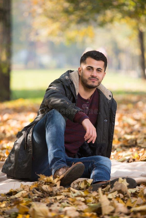 Πορτρέτο του όμορφου νεαρού άνδρα στο πάρκο φθινοπώρου στοκ εικόνες