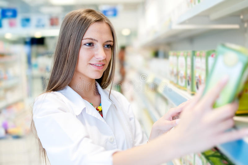 Πορτρέτο του όμορφου ξανθού θηλυκού φαρμακοποιού που διαβάζει μια ετικέτα στοκ φωτογραφία