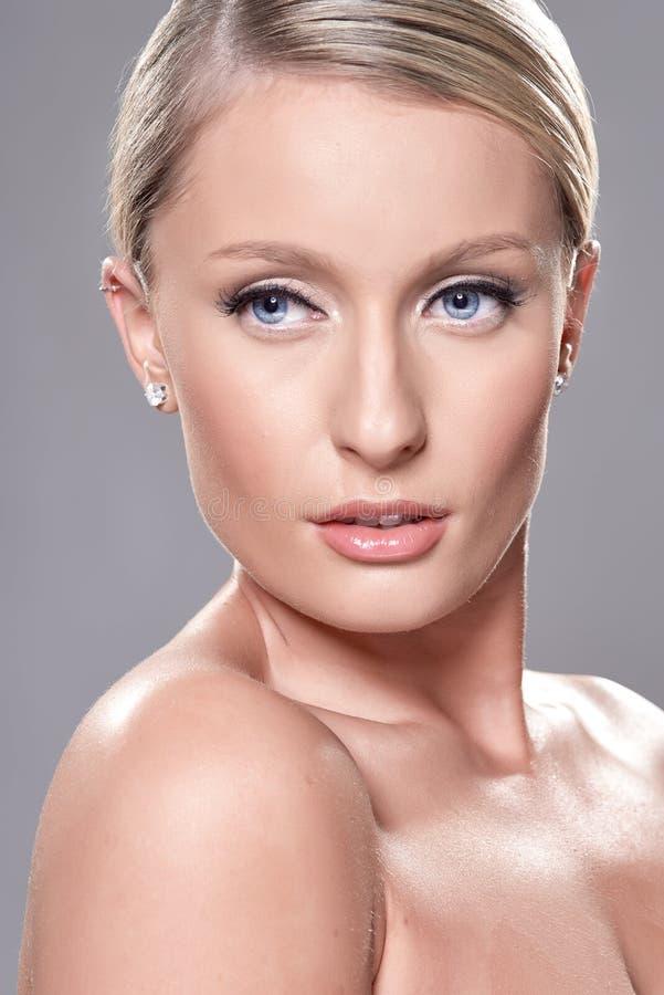 Πορτρέτο του όμορφου ξανθού προτύπου με τα μπλε μάτια, στο γκρίζο backgr στοκ εικόνα