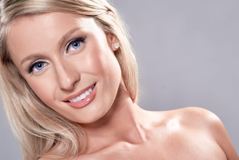 Πορτρέτο του όμορφου ξανθού προτύπου με τα μπλε μάτια, στο γκρίζο backgr στοκ φωτογραφία