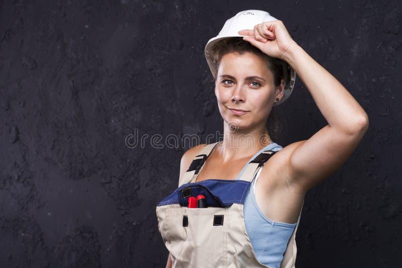 Πορτρέτο του όμορφου οικοδόμου εργαζομένων γυναικών σε ομοιόμορφο με το άσπρο κράνος χαριτωμένο νέο κορίτσι οικοδόμων στα ενδύματ στοκ φωτογραφία με δικαίωμα ελεύθερης χρήσης