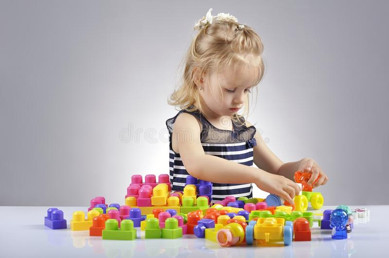 Πορτρέτο του όμορφου παιχνιδιού μικρών κοριτσιών με τους πλαστικούς κύβους παιχνιδιών στοκ φωτογραφίες με δικαίωμα ελεύθερης χρήσης