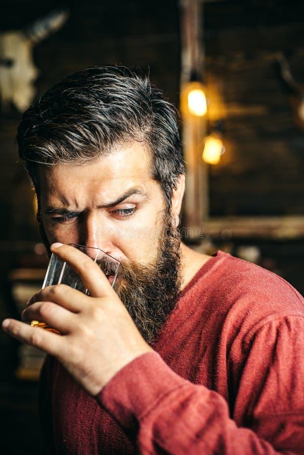 Πορτρέτο του όμορφου ποτηριού εκμετάλλευσης νεαρών άνδρων του κονιάκ κονιάκ whiskeyand Κομψό άτομο που κρατά ένα ποτήρι του ποτού στοκ εικόνα
