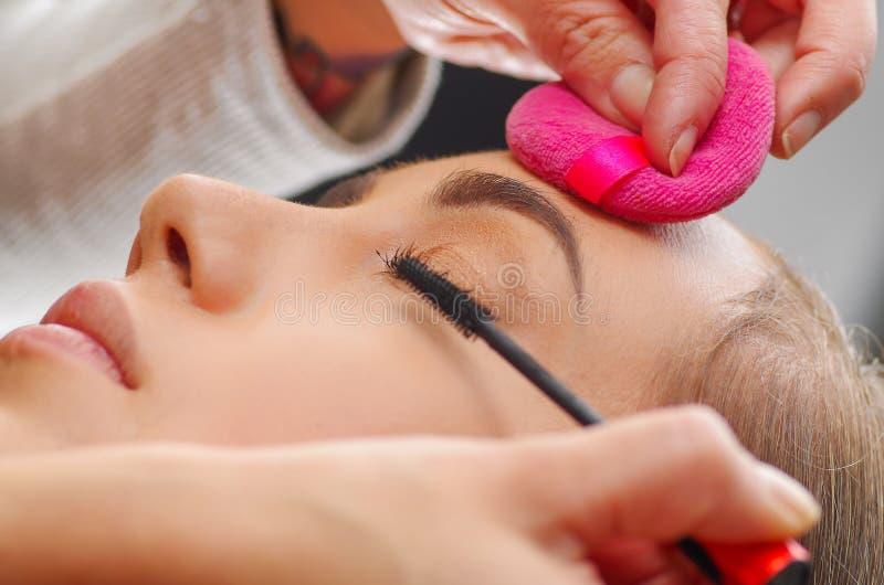Πορτρέτο του όμορφου προσώπου της νέας γυναίκας που παίρνει τη σύνθεση Ο καλλιτέχνης εφαρμόζει mascara ματιών στα μάτια της Η κυρ στοκ φωτογραφίες