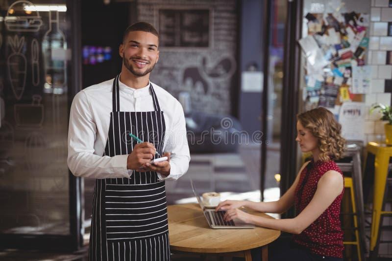 Πορτρέτο του όμορφου σερβιτόρου με το σημειωματάριο από το θηλυκό πελάτη που χρησιμοποιεί το lap-top στοκ εικόνες