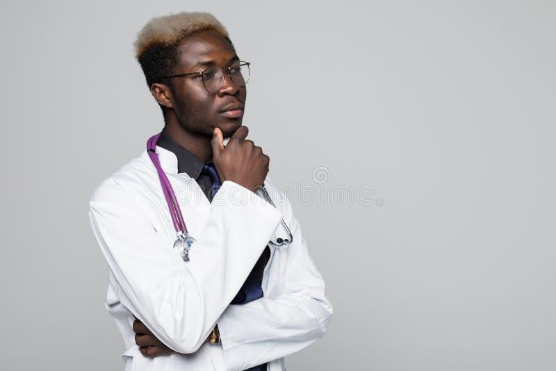 Πορτρέτο του όμορφου σκεπτικού αμερικανικού γιατρού Afro στο άσπρο παλτό που κρατά το χέρι στο πηγούνι του, που κοιτάζει μακριά κ στοκ φωτογραφίες