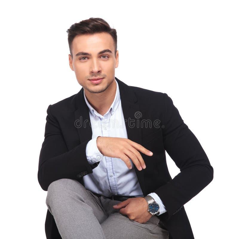 Πορτρέτο του όμορφου στηργμένος χεριού επιχειρηματιών στο γόνατο ενώ sitt στοκ εικόνες