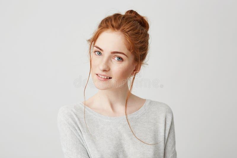 Πορτρέτο του όμορφου τρυφερού redhead χαμόγελου κοριτσιών που θέτει την εξέταση τη κάμερα πέρα από το άσπρο υπόβαθρο στοκ εικόνα με δικαίωμα ελεύθερης χρήσης