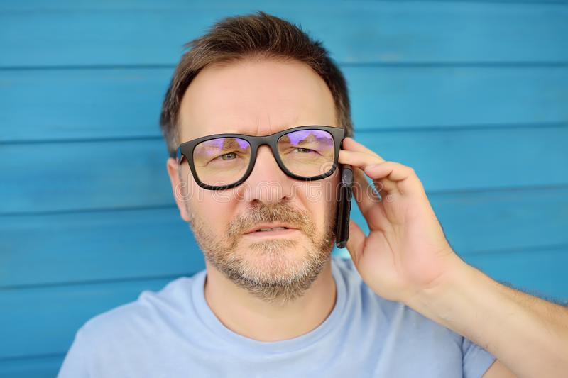 Πορτρέτο του όμορφου ώριμου ατόμου που μιλά στο τηλέφωνο κινητή τηλεφωνική τεχνολογία απεικόνισης επικεφαλίδων σφαιρών σχεδίων επ στοκ φωτογραφία με δικαίωμα ελεύθερης χρήσης