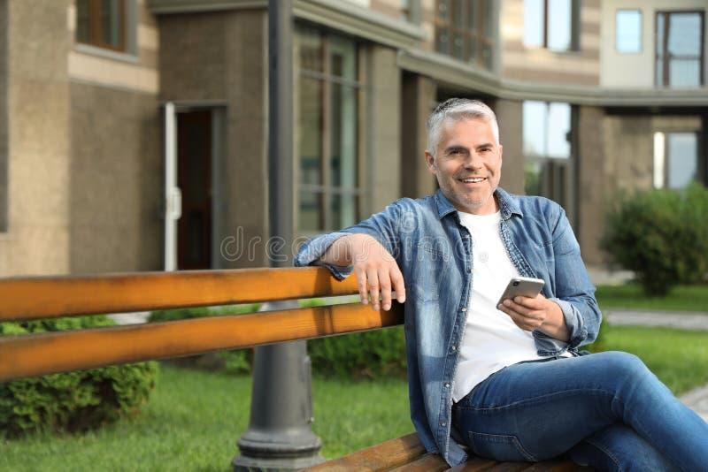 Πορτρέτο του όμορφου ώριμου ατόμου που χρησιμοποιεί το κινητό τηλέφωνο στην πόλη στοκ φωτογραφία