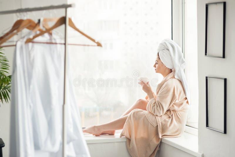 Πορτρέτο του όμορφων κοριτσιού και της πετσέτας στο κεφάλι στο μπουρνούζι με ένα φλυτζάνι, έννοια χαλάρωσης εγχώριου ύφους μετά α στοκ φωτογραφίες