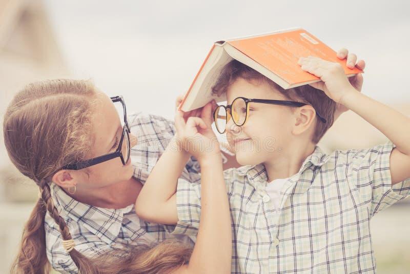 Πορτρέτο του όμορφων σχολικών αγοριού και του κοριτσιού που φαίνονται πολύ ευτυχών έξω στοκ εικόνες