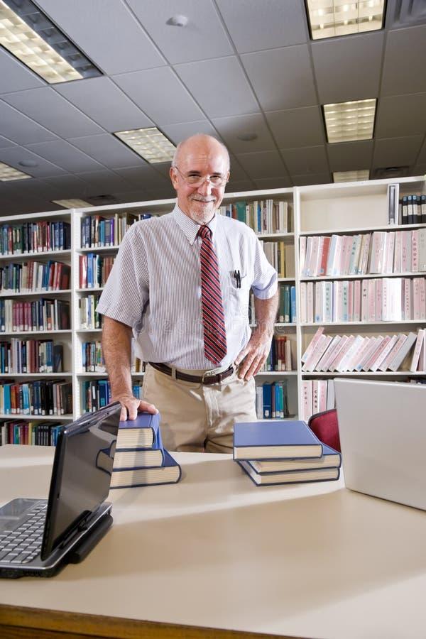 Πορτρέτο του ώριμου ατόμου στη βιβλιοθήκη με τα εγχειρίδια στοκ εικόνα