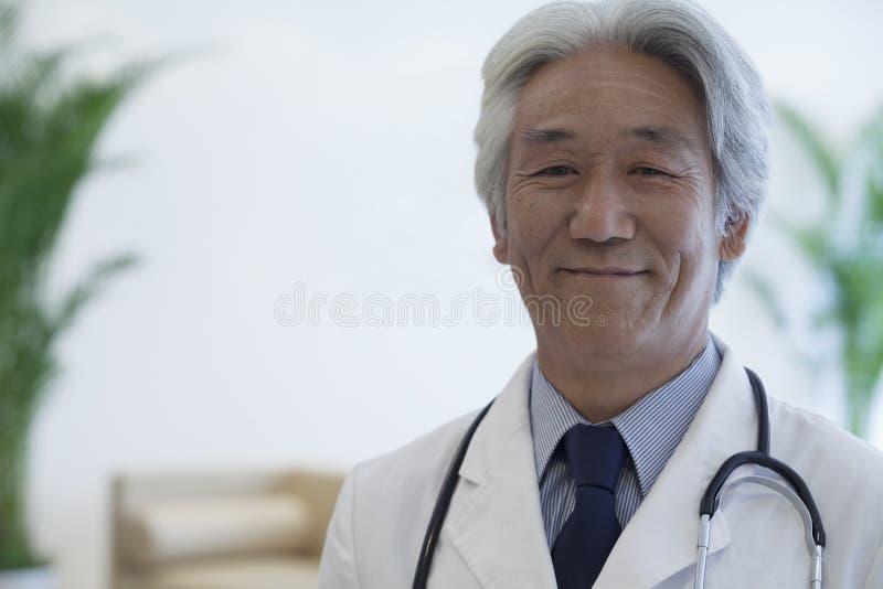 Πορτρέτο του ώριμου γιατρού που εξετάζει τη κάμερα και το χαμόγελο στοκ φωτογραφία με δικαίωμα ελεύθερης χρήσης