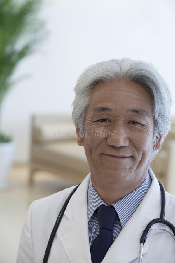 Πορτρέτο του ώριμου γιατρού που εξετάζει τη κάμερα και το χαμόγελο στοκ εικόνα με δικαίωμα ελεύθερης χρήσης