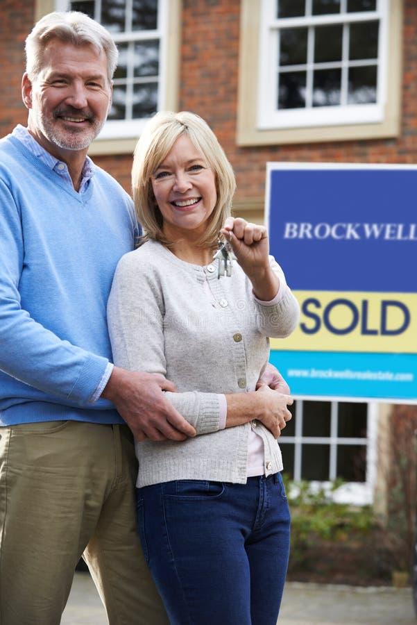 Πορτρέτο του ώριμου ζεύγους με τα κλειδιά για το νέο σπίτι στοκ φωτογραφίες
