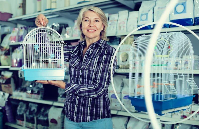 Πορτρέτο του ώριμου κλουβιού πουλιών γυναικών αγοράζοντας στο petshop στοκ εικόνα