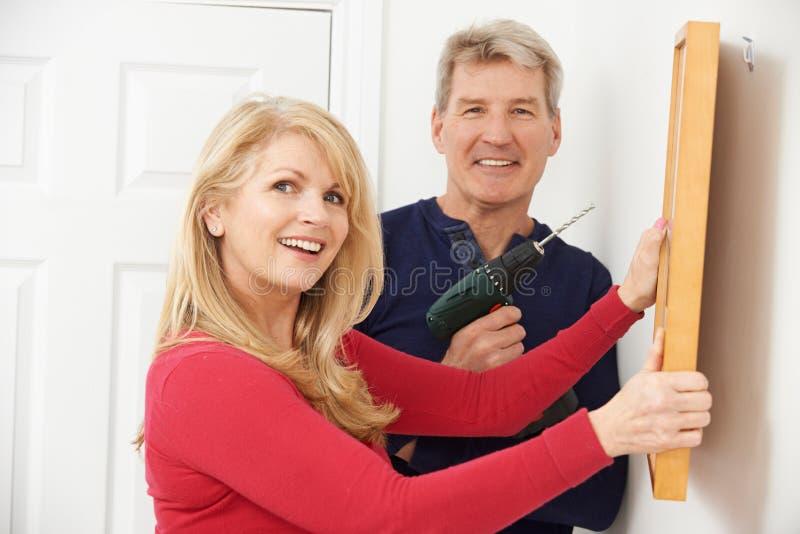 Πορτρέτο του ώριμου τρυπώντας με τρυπάνι τοίχου ζεύγους για να κρεμάσει το πλαίσιο εικόνων στοκ εικόνα