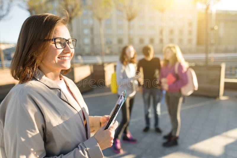 Πορτρέτο του ώριμου χαμογελώντας θηλυκού δασκάλου στα γυαλιά με την περιοχή αποκομμάτων, outdor με μια ομάδα σπουδαστών εφήβων στοκ φωτογραφίες