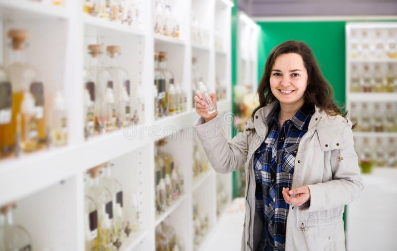 Πορτρέτο του brunette που ψωνίζει στο κατάστημα αρώματος στοκ εικόνες