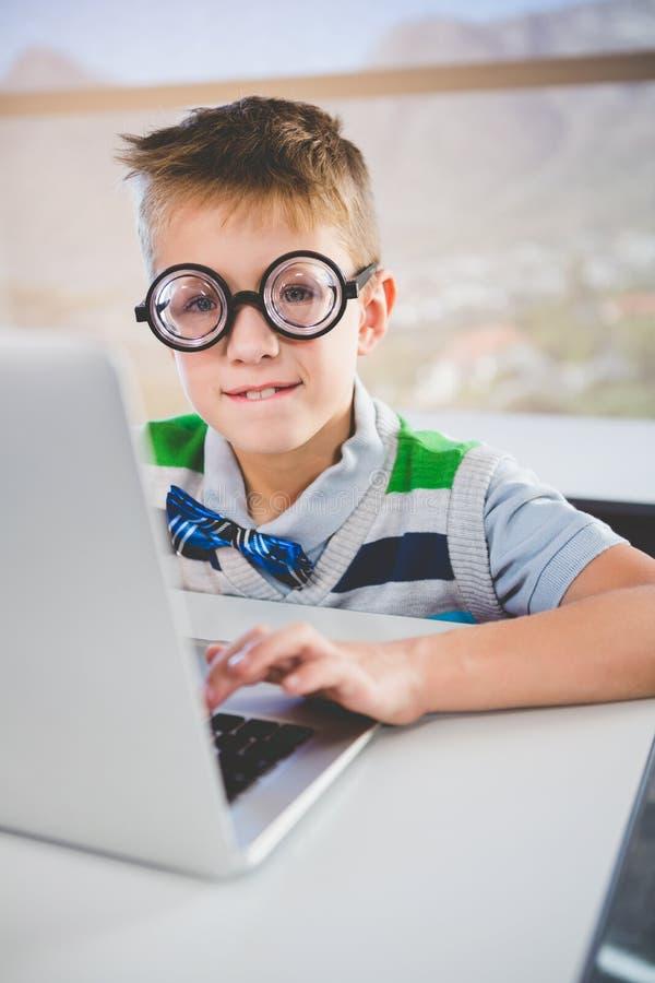 Πορτρέτο του schoolkid που χρησιμοποιεί το lap-top στην τάξη στοκ φωτογραφία