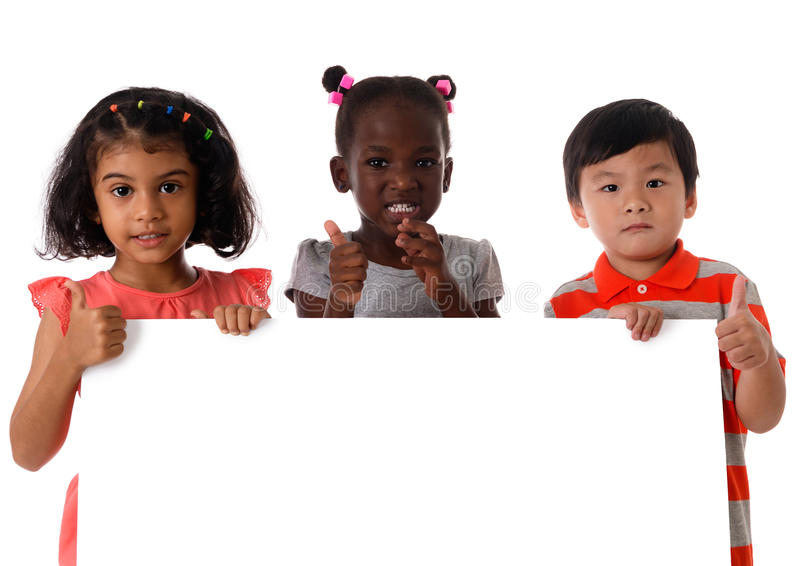 Πορτρέτο τρία των πολυφυλετικών παιδιών στο στούντιο με το λευκό πίνακα απομονωμένος στοκ φωτογραφίες