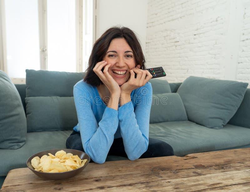 Πορτρέτο τρόπου ζωής της εύθυμης νέας συνεδρίασης γυναικών στον καναπέ που προσέχει τη TV τον τηλεχειρισμό στοκ εικόνες