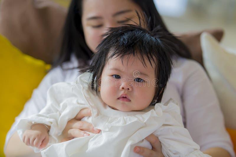 Πορτρέτο τρόπου ζωής της νέας ευτυχούς και χαριτωμένης ασιατικής κινεζικής γυναίκας που παίζει και που κρατά το γλυκό λατρευτό κο στοκ φωτογραφία
