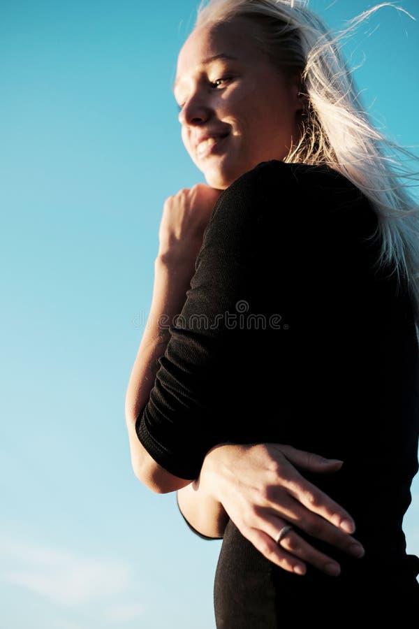 Πορτρέτο τρόπου ζωής της νέας ξανθής γυναίκας με το χαμόγελο στο μαύρο φόρεμα στοκ εικόνα