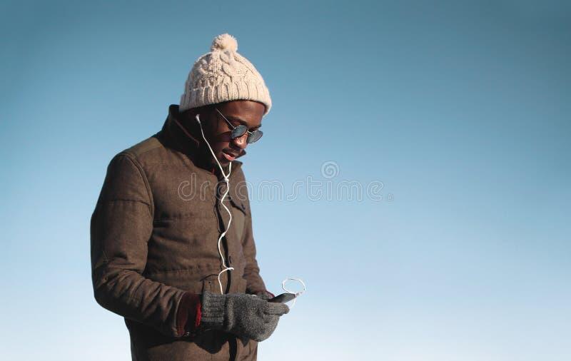 Πορτρέτο τρόπου ζωής του νέου αφρικανικού ατόμου που απολαμβάνει τη μουσική ακούσματος στοκ εικόνες