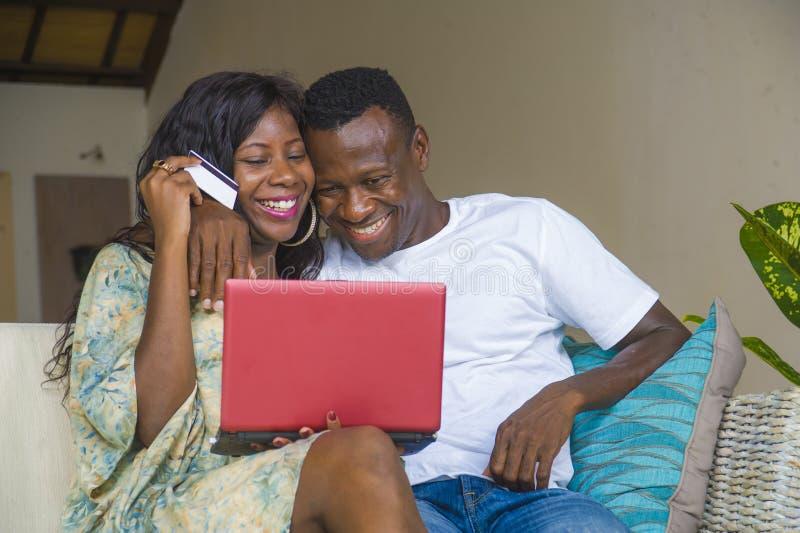 Πορτρέτο τρόπου ζωής του νέου ευτυχούς και ελκυστικού αμερικανικού ζεύγους μαύρων Αφρικανών που απολαμβάνει στο σπίτι την πιστωτι στοκ φωτογραφίες