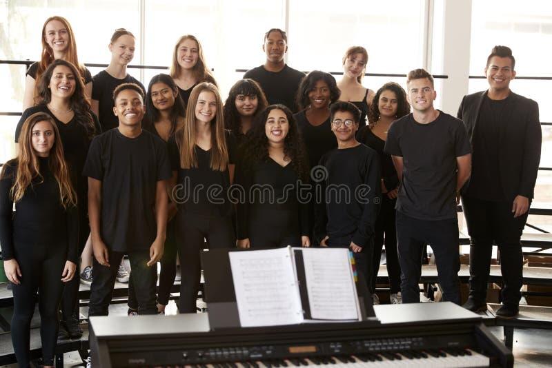 Πορτρέτο των αρσενικών και γυναικών σπουδαστών που τραγουδούν στη χορωδία με το δάσκαλο στο σχολείο τεχνών προς θέαση στοκ εικόνες
