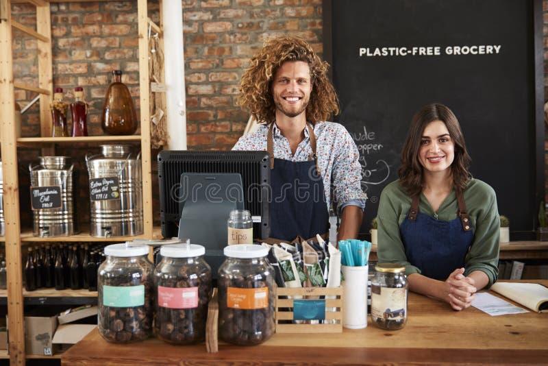Πορτρέτο των αρσενικών και θηλυκών ιδιοκτητών του βιώσιμου πλαστικού ελεύθερου μανάβικου πίσω από το γραφείο πωλήσεων στοκ εικόνες