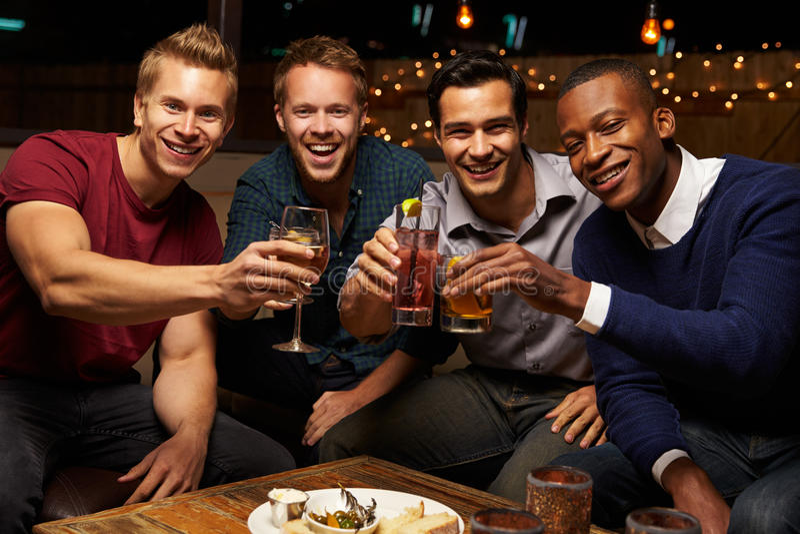 Πορτρέτο των αρσενικών φίλων που απολαμβάνουν τη νύχτα έξω στο φραγμό στεγών στοκ φωτογραφίες με δικαίωμα ελεύθερης χρήσης