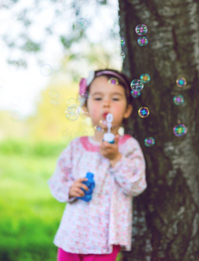 Πορτρέτο των αστείων καλών φυσαλίδων σαπουνιών μικρών κοριτσιών φυσώντας στο πάρκο στοκ φωτογραφία