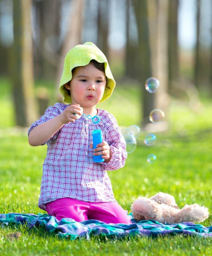 Πορτρέτο των αστείων καλών φυσαλίδων σαπουνιών μικρών κοριτσιών φυσώντας στο πάρκο στοκ εικόνα