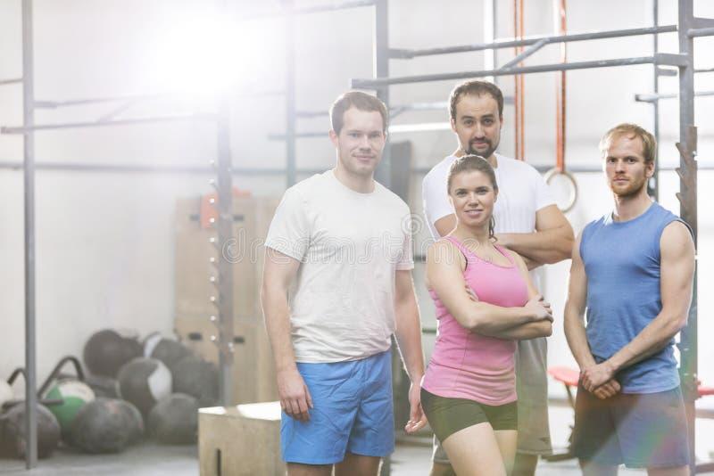 Πορτρέτο των βέβαιων ανδρών και των γυναικών που στέκονται στη γυμναστική crossfit στοκ εικόνα με δικαίωμα ελεύθερης χρήσης